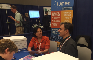A man and a woman talking at an exhibit hall table at the SXSWedu conference in 2016