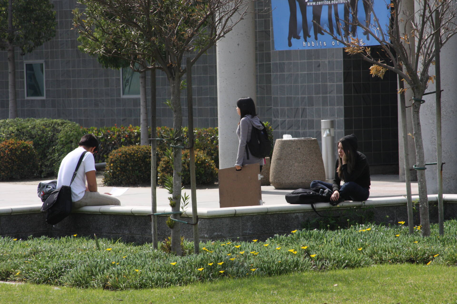 Two Cerritos College students, a young man and a young woman, sit on a low stone wall outside a gray classroom building. A third woman is passing by them on the sidewalk, carrying an artist's portfolio.