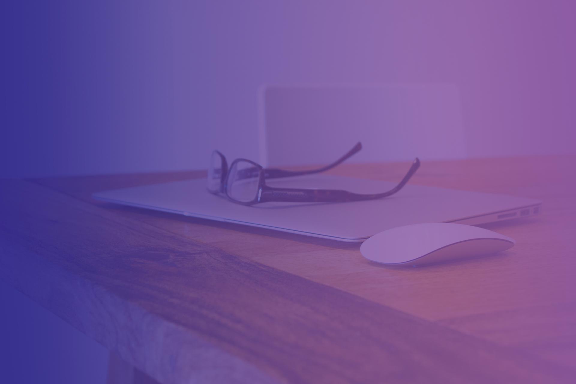 eyeglasses atop closed laptop on blonde wood desk