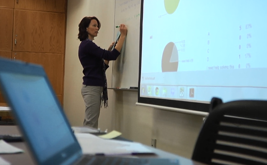 Female professor writing on a whiteboard, next to a screen projection of instructional materials for a math class.