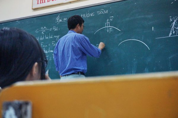 Photograph of a professor writing on a chalkboard.