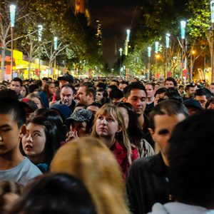 People on a crowded pedestrian street that is lit festively at night