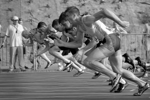 Black and white photograph of a line up of several runners at the start of a race.