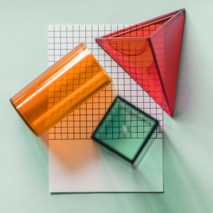 A piece of graph paper with a red pyramid, an orange cylinder, and a green cube on top.