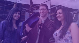 Two young women and a young man stand in front of a glass-walled building. They're all smiling, and the young man holds a dark blue mortarboard (the cap students wear at graduation).
