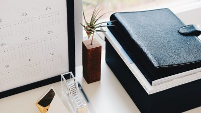 Calendar, tape, plant, and notebooks placed on a desk