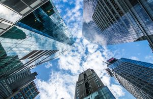 Photograph looking up at five tall buildings.