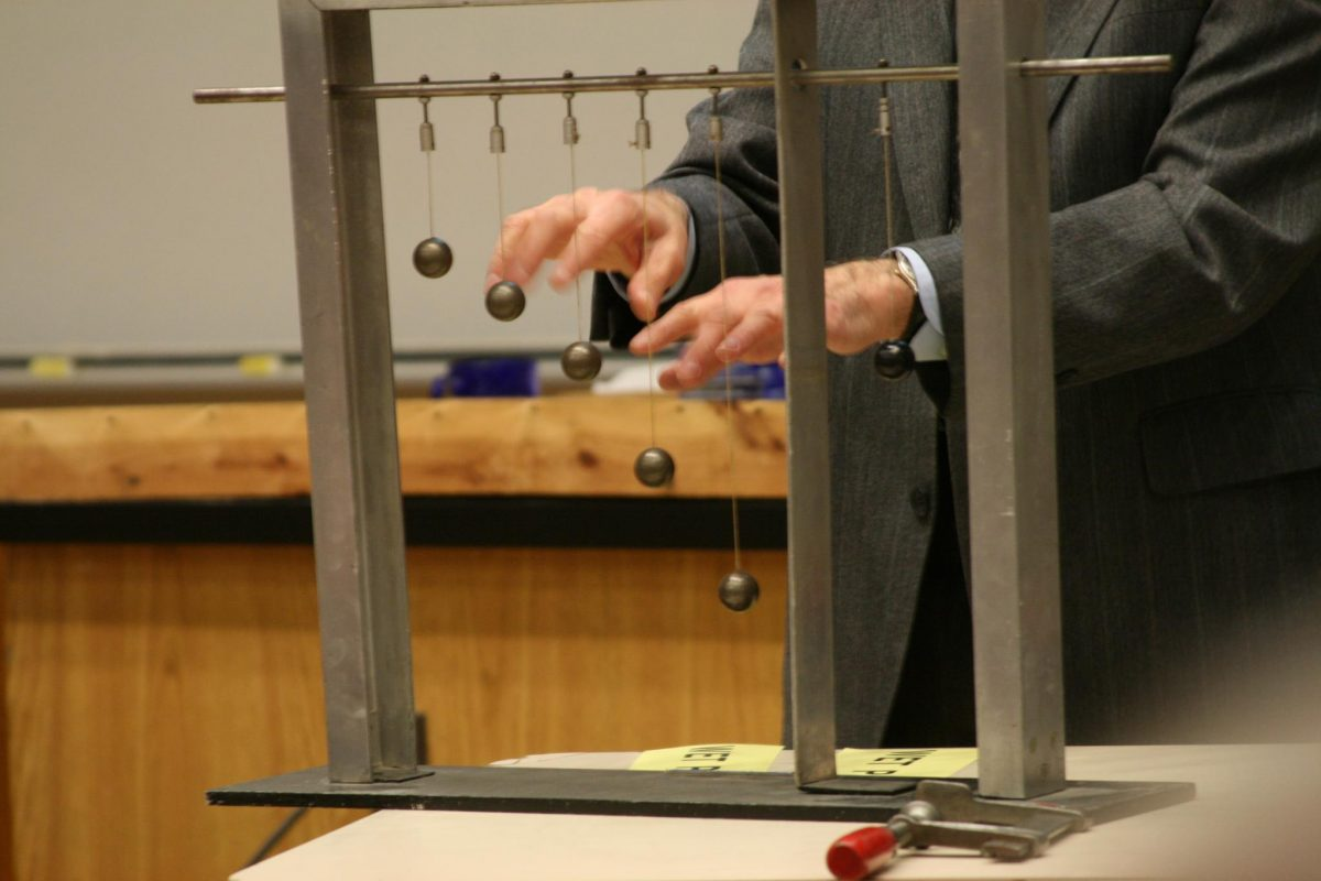 A professor demonstrates a physics experiment using a set of hanging pendulums