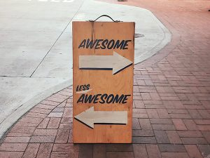 """Sandwich board with one arrow pointing towards """"Awesome"""" and a second arrow pointing towards """"Less Awesome"""""""