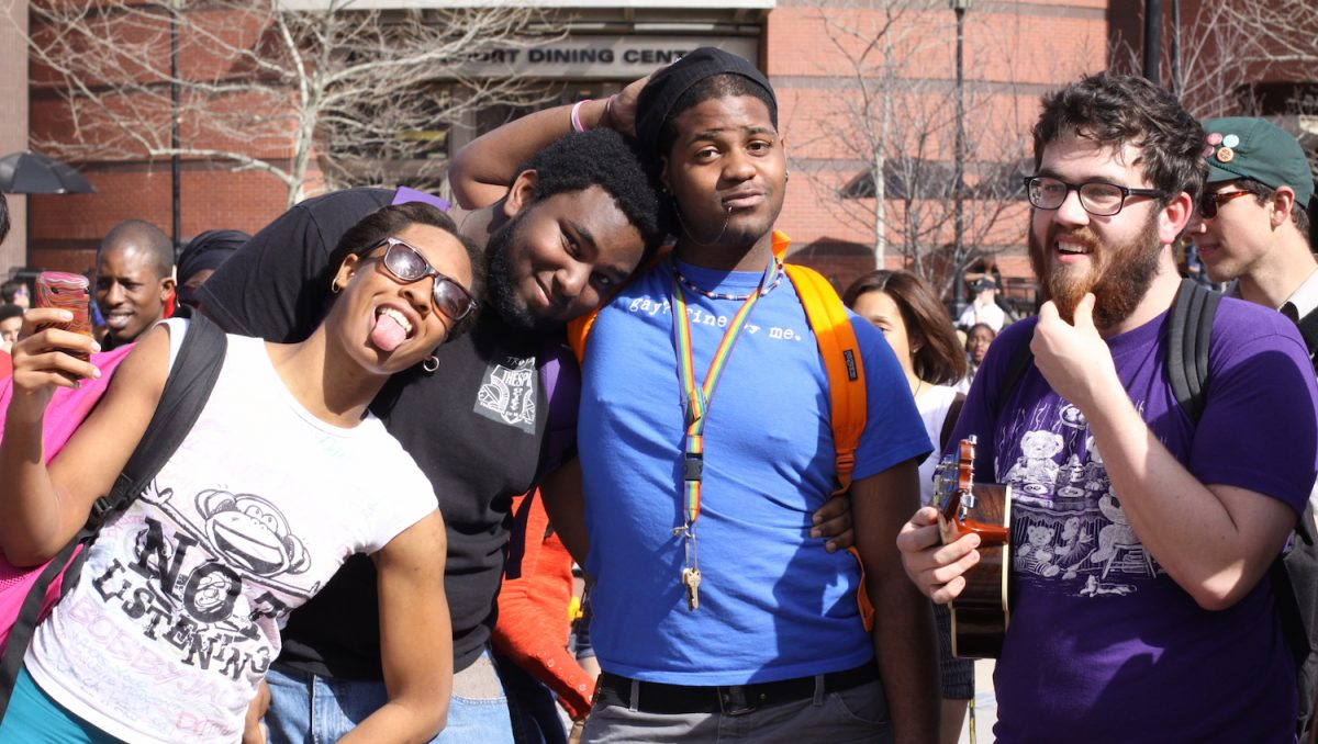 An ethnically diverse group of young male and female college students clowning for the camera