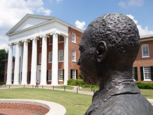 Bronze statue of James Meredith in the foreground, with the white columns and red brick of the University of Mississippi's Lyceum in the background
