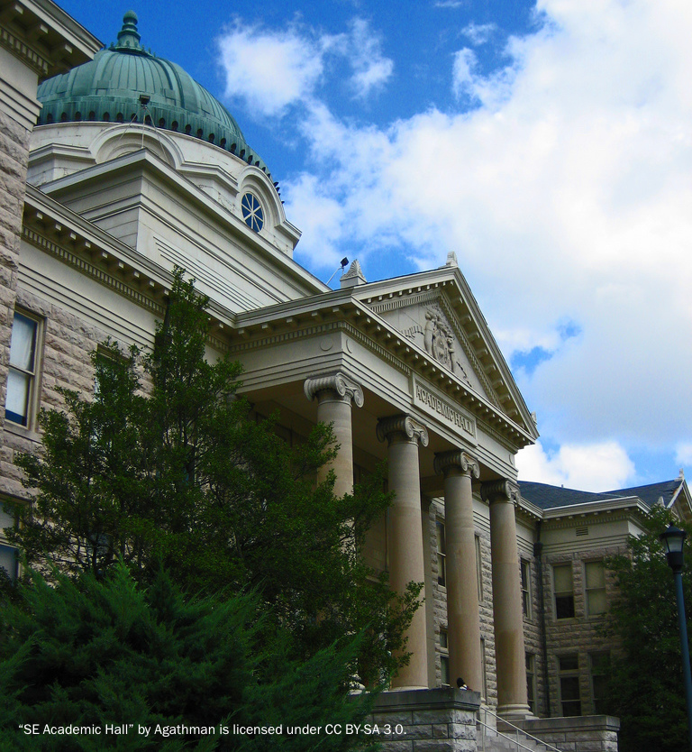A grand, historic university building of white stone built in classical style with four marble columns at the main entrance and a copper dome.